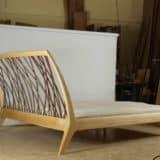 Bei diesem Bett aus Massivholz ist das Kopfteil in einem eleganten Schwung nach hinten gebogen