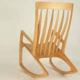 Schaukelstuhl aus Holz, die Sitzfläche geht in die Kufen über