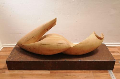 Die Skulptur besteht aus zwei Massiv - Holzteilen, der Sockel aus unbehandeltem Stahl
